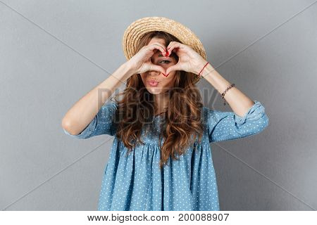 Image of happy young pretty woman standing over grey wall wearing hat showing heart gesture. Looking camera.