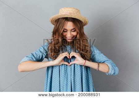 Image of happy young pretty woman standing over grey wall wearing hat showing heart gesture. Looking aside.