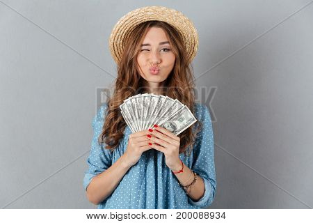 Picture of young funny woman standing over grey wall wearing hat holding money. Looking camera.