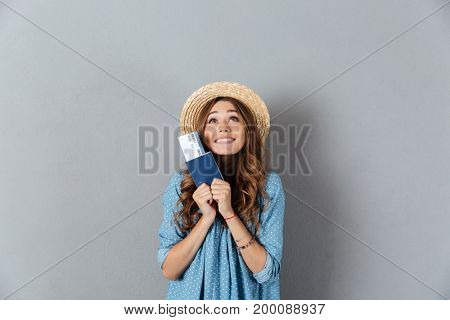 Image of happy young pretty woman standing over grey wall wearing hat holding passport and ticket. Looking aside.
