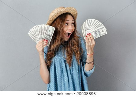 Picture of excited young happy woman standing over grey wall wearing hat holding money. Looking aside.