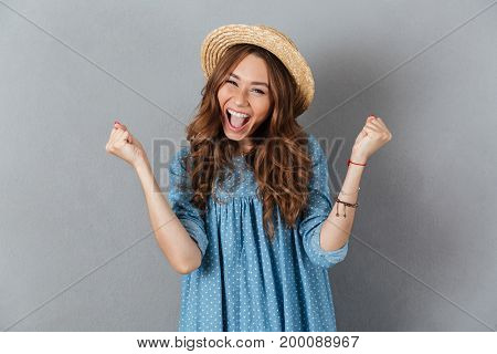 Image of smiling young pretty woman standing over grey wall wearing hat showing winner gesture. Looking camera.