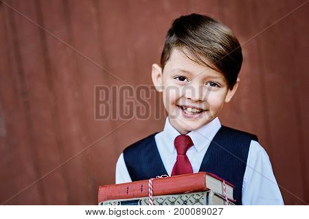 Portrait of a happy school boy standing with book on red wooden background.. Farewell Bell. day of knowledge. beginning of the school year.