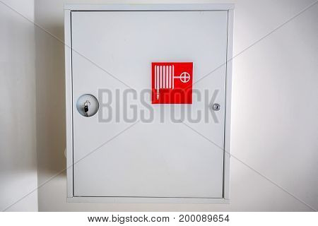 Close up white cabinet for fire hydrant on white wall