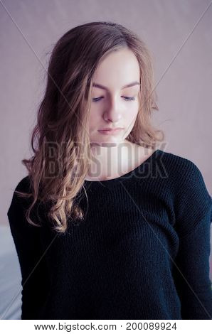 Attractive teenager model wearing stylish black top looking down with shy and dreamy expression on her face. Headshot of student girl with curly fair hair and clean healthy skin and no make up.