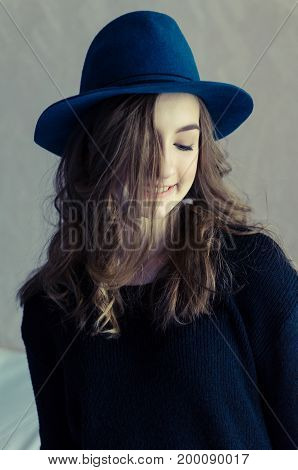 Portrait of beautiful smiling hipster teenage girl with long fair curly hair in a blue hat and black jumper looking down. Lifestyle and people concept. Toned image.
