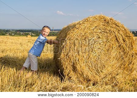 In the summer boy in a field near a hay bale