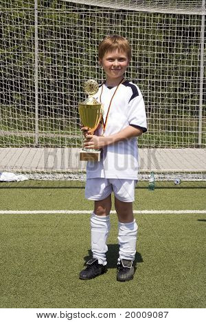 Young Boy In Soccer Dress Presents Proud The Cup