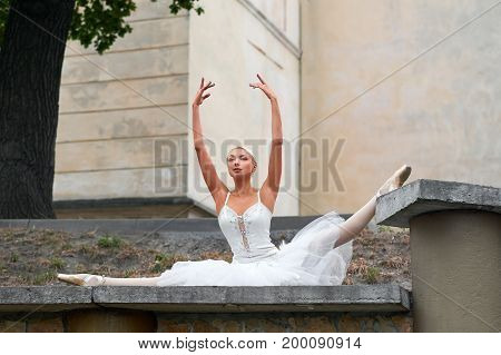 Stunning young ballerina performing outdoors in the city doing splits flexibility fitness athletics active people.