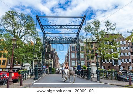 Amsterdam the Netherlands - 13 August 2017: people crossing bridge on the Prinsengracht