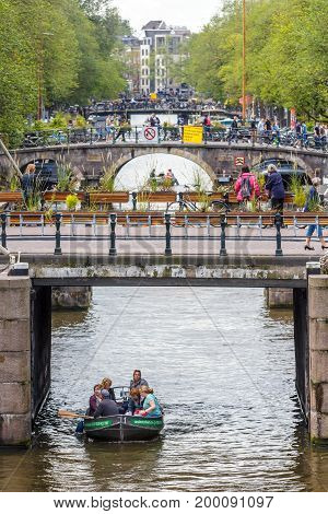 Amsterdam the Netherlands - 13 August 2017: people crossing bridges on the Prinsengracht with boats on canal