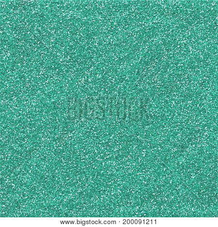 A digitally created aqua green sparkling glitter paper background texture.