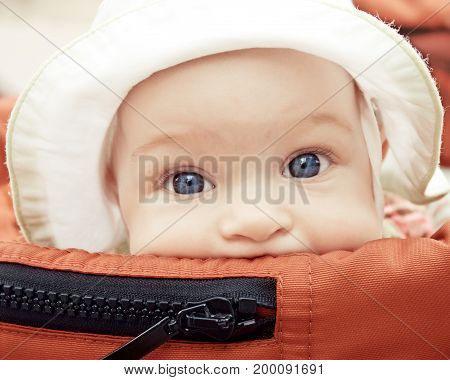 Portrait of funny baby in buggy outdoor