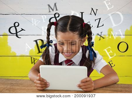 Digital composite of Many letters around Girl on tablet in front yellow painted background