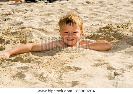 Boy Is Digging Oneself Into The Sandy Beach And Has A Lot Of Fun