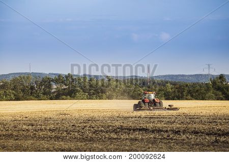 Tractor driving in field autumn rural landscape. Agriculture