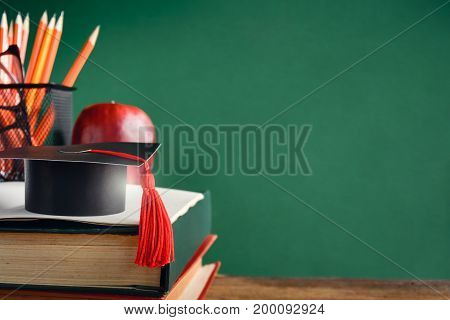 Graduate Cap And Apple On Old Book At Library Green Wall Background