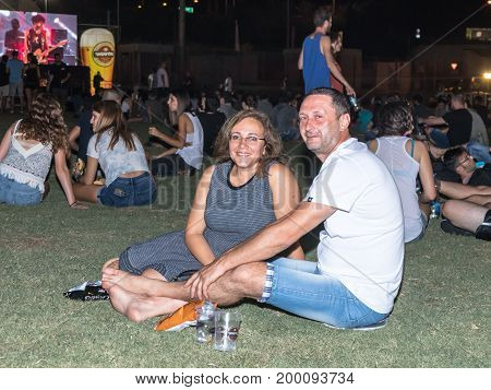 Haifa Israel August 16 2017 : Satisfied visitors sit on the grass and rest at the traditional annual beer festival in the city of Haifa in Israel