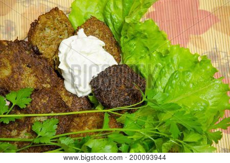 Potato pancakes with sour cream and greens.