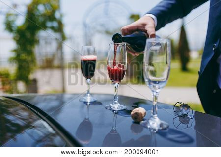 A Man Pours Champagne Into The Crystal Glasses On The Hood Of The Car