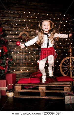 Baby Girl 4-5 Year Old Jumping In Room Over Christmas Tree With Decorations. Looking At Camera. Merr
