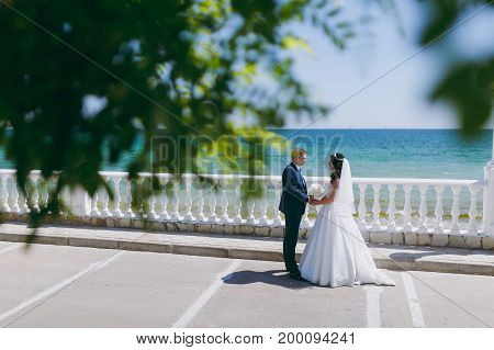 Groom And Bride On A Walk Outdoors At The Sea