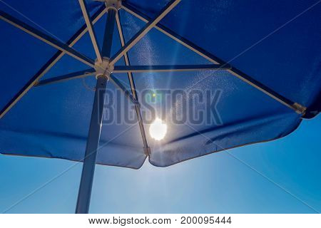 The sun shines through blue umbrella on the beach.