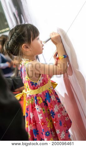 asian girl in colorful dress writing some message on the sign board in wedding reception.