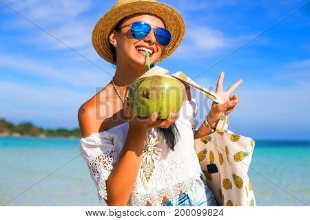 Portrait of a sunburnt young cute happy girl on the beach, ocean. Dressed in denim shorts, top, straw hat, sunglasses, a bag with pineapple, drinking coconut, laughing, relaxing on a tropical island