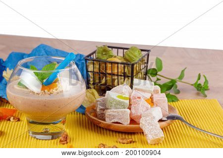 A wooden table with a plate of Turkish delight, rahat lokum or lokum, dried apricots, walnuts, green leaves of mint, metallic spoon and physalis on a physalis on a colored background, isolated on a white.