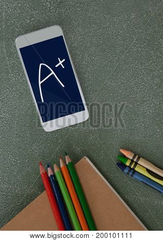 Digital composite of Phone on a school table with A+ text on screen