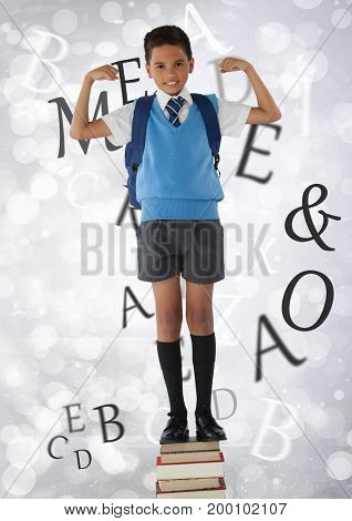 Digital composite of Many letters around Schoolboy flexing strong arms while standing on books and bokeh bright backgroun