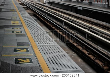 Yellow line and arrow with railway on skytrain station Bangkok Thailand.
