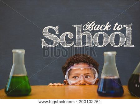 Digital composite of Student boy hiding behind a table against blue blackboard with back to school text