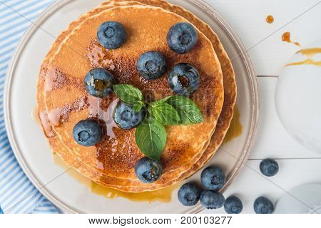 Stack of pancakes with fresh blueberry and caramel syrup. Top view