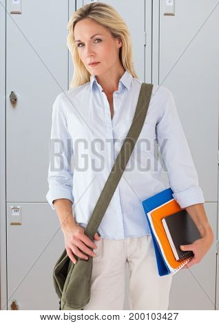 Digital composite of male student holding books in front of lockers