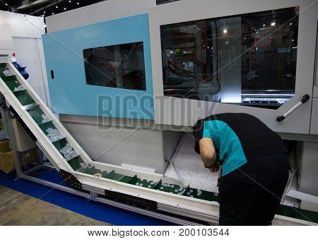 A Worker operating bottle cap making machine