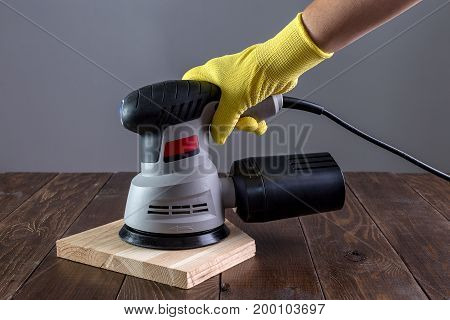 A hand grinder in the hand on a wooden surface.