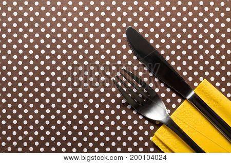 Fork and knife lying on yellow serviettes on brown cardboard with white dots.