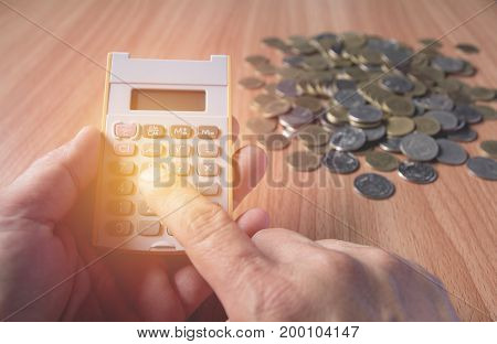 Hand of man are pressing the calculator with coins on the wooden table. Man pressing calculator button. Financial analyzing concept.
