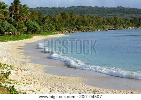 Scenic beach with gentle foaming waves rolling onto the shore with white sands and gentle waves in a tropical island