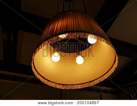 Close up of stylish oval lampshade suspended from the ceiling with ruffles around the border