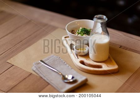 A close-up picture of beautiful lunch composition. A healthy salad with creamy sauce and a nutritious milkshake on a wooden table background. A set of organic dishes and a spoon. Copy space.