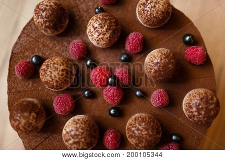 Close-up of a sweet chocolate tiramisu cake, sprinkled with cocoa powder and decorated with succulent bright raspberries and black currants on a blurred wooden background, top view. Sweets concept.