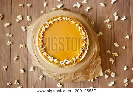 Close-up of a round cake with condensed milk, honey and a shortbread decorated with sweet popcorn on a paper stand and on a blurred wooden background. Sweet and tasty dessert with popcorn, top view.