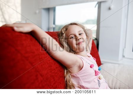 Happy 6 year old girl is sitting on red chair in his room