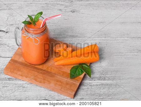 A view from above on a mason jar full of a thick blended orange beverage. A detox carrot smoothie drink with straws on a gray table background. A juicy cocktail next to ripe carrot tubes. Copy space.