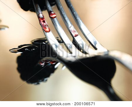 A Fork on a Reflective Surface Squishing a Berry