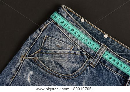 Close up of jeans belt loops and pocket. Top part of denim trousers isolated on black background. Jeans with blue measure tape instead of belt. Healthy lifestyle and dieting concept.