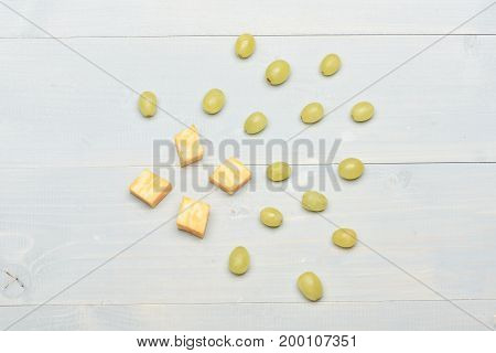 Gourmet food concept. Several white grapes top view. Composition of marble cheese and grapes scattered on vintage surface. Delicious snack with cheese and summer fruit close up.